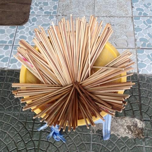 Random bucket of chop sticks on the pavement!